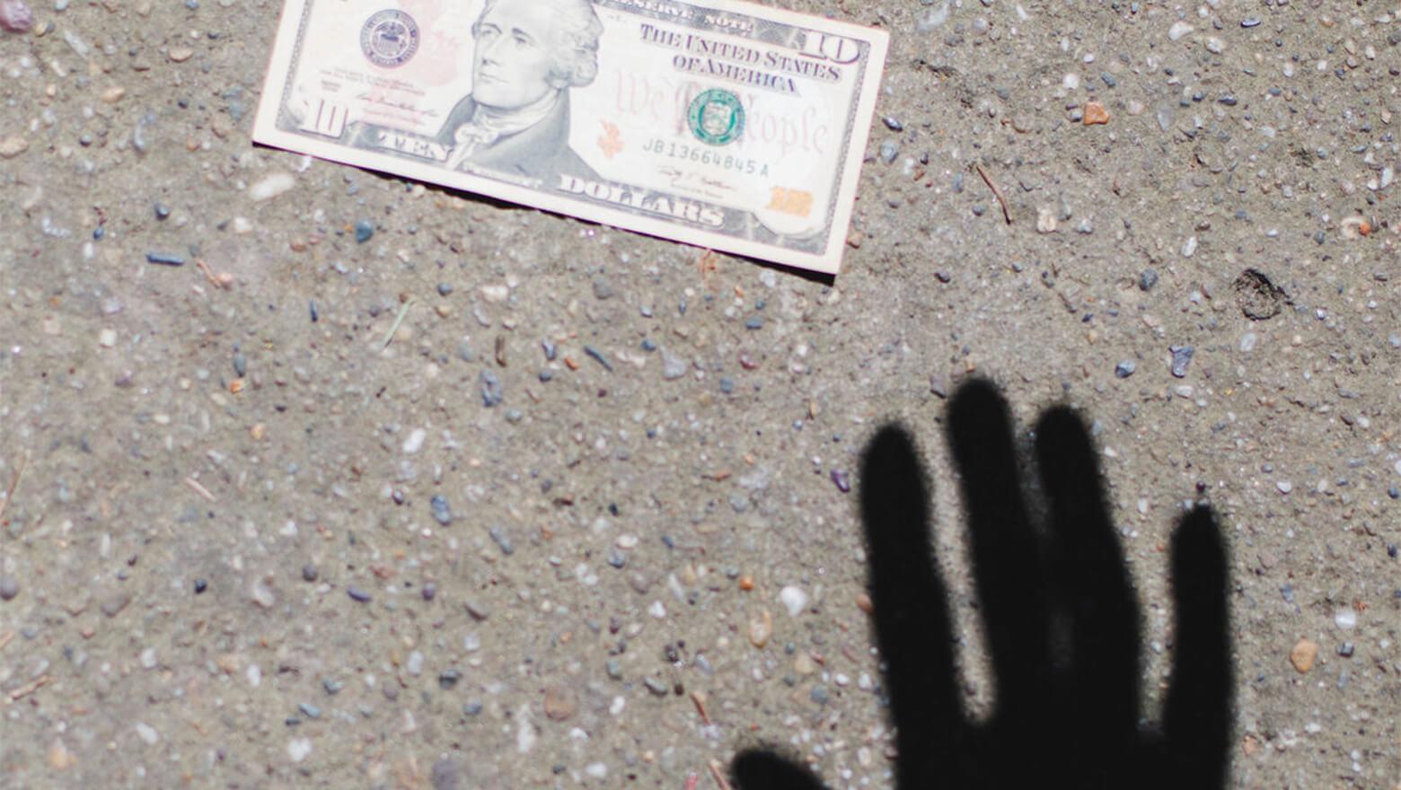 hand shadow with 10 dollar bill